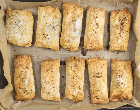 Photo for Plate with baked puff pastry pies,top view - Royalty Free Image