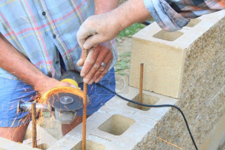 bricklayer builds a wall, rebar cutting angle grinder