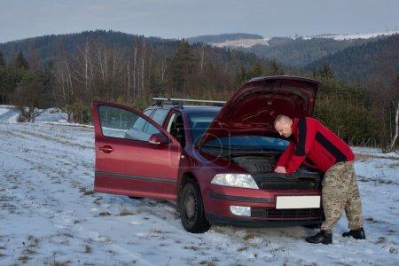 Mann repariert Auto auf verlassener Straße, Winterwetter