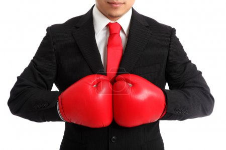Photo for Businessman wearing red boxing gloves and a black suit with a red tie. White background - Royalty Free Image
