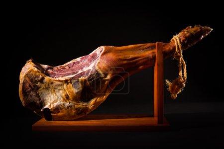 Photo for Jamon serrano. A Spanish ham on black. - Royalty Free Image