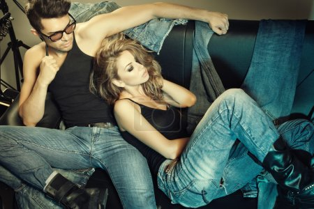 Photo for Sexy man and woman dressed in jeans doing a fashion photo shoot in a professional studio - Royalty Free Image