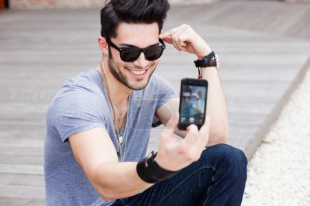 Young male model photographing himself with a smartphone