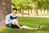 Muž, který držel knihu na trávě v parku