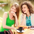 Two beautiful women laughing over a cofee at the r...