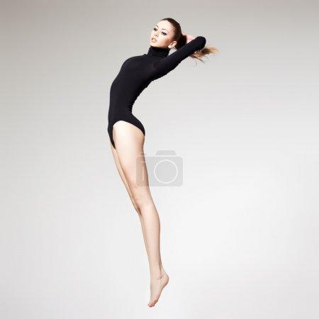 Photo pour Belle femme avec un corps mince parfait et de longues jambes sautant - concept de fitness - image libre de droit