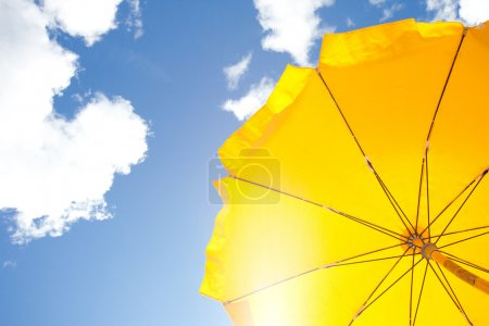 Photo for Yellow umbrella on blue sky with clouds - Royalty Free Image