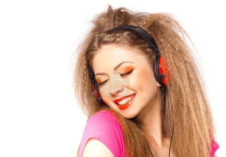 Photo pour Jolie fille blonde frisée, écouter de la musique sur le grand casque rouge - image libre de droit