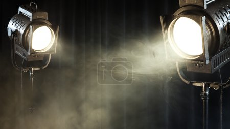 Vintage theatre spot light on black curtain with s...