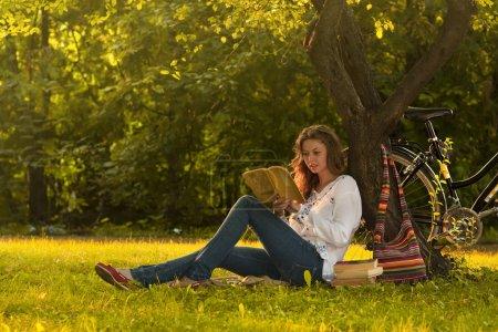 Photo pour Fille lisant un livre dans le parc - image libre de droit