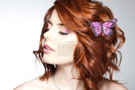 Photo for Pretty woman with a butterfly in her hair - beauty shot - Royalty Free Image