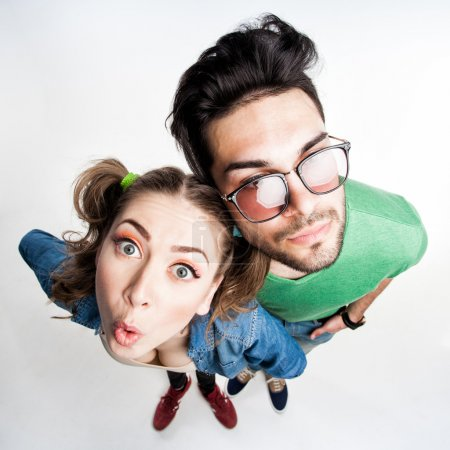 Photo for Pretty couple dressed casual making funny faces - view from above wide angle shot - Royalty Free Image