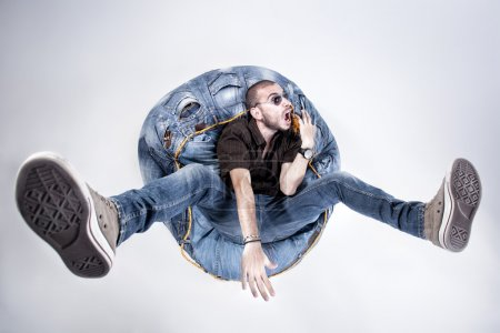 Funny crazy man dressed in jeans and sneakers standing on denim beanbag