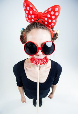 cute girl with a big red lollipop and funny sunglasses