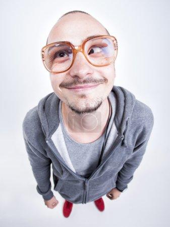 Photo pour Un homme drôle avec grandes lunettes cross regardant et souriant - image libre de droit