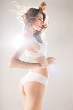 Beautiful woman with perfect body dressed in white lingerie