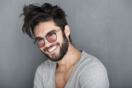 Photo for Sexy man with beard smiling big against wall - Royalty Free Image