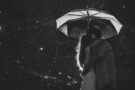 Silhouette of kissing couple under umbrella...