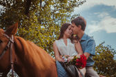 Young beautiful couple  with a horse. Filtered. Selective focus.