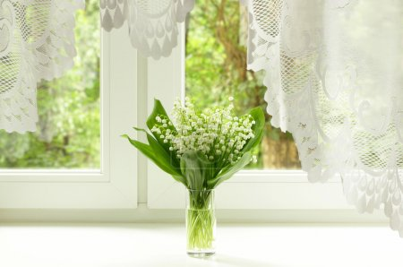 Bouquet of lily of the valley on the windowsill