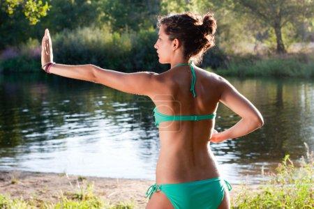 Girl in bikini practicing tai chi next to a river
