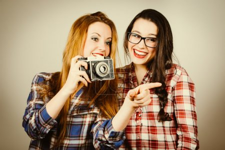 Photo for Funny hipster girls with plaid shirt and retro eye glasses taking pictures with an old film camera.Retro filter effect added. - Royalty Free Image