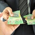 Businessman hand giving money  - Australian dollar...