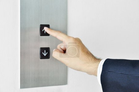 Businessman hand touching going up sign on lift co...