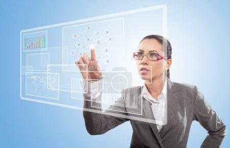Foto de Empresaria presionando un botón en una interfaz de pantalla futurista - Imagen libre de derechos