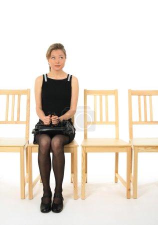 Photo pour Anxieuse jeune femme assise sur une chaise et attendre. - image libre de droit