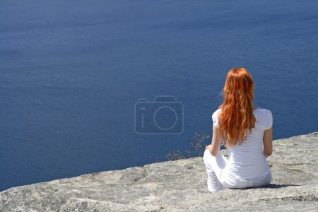 Red-haired girl looking over blue water