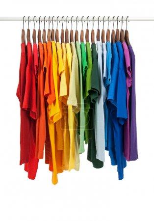 Photo pour Couleurs de l'arc-en-ciel. variété de chemises sport sur des cintres en bois, isolés sur blanc. - image libre de droit