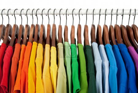 Photo for Rainbow colors. Choice of casual clothes on wooden hangers, isolated on white. - Royalty Free Image