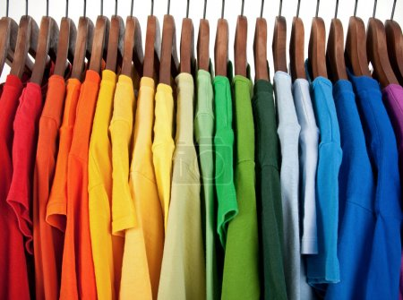 Photo for Colors of rainbow. Variety of casual clothes on wooden hangers, isolated on white. - Royalty Free Image