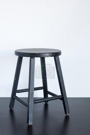 Photo pour Tabouret shabby noir peint sur une surface en bois . - image libre de droit