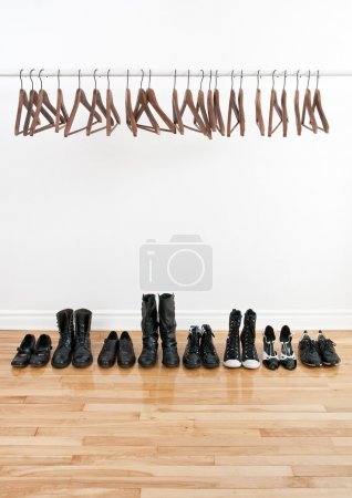 Photo for Row of black shoes and boots on a wooden floor, and empty hangers on a rod. - Royalty Free Image