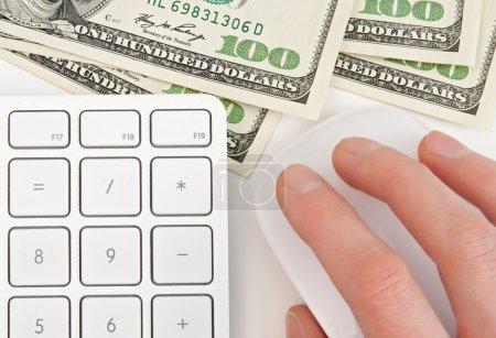 Photo pour Cent billets d'un dollar, calculatrice clavier et femelle à la main sur la souris d'ordinateur. - image libre de droit