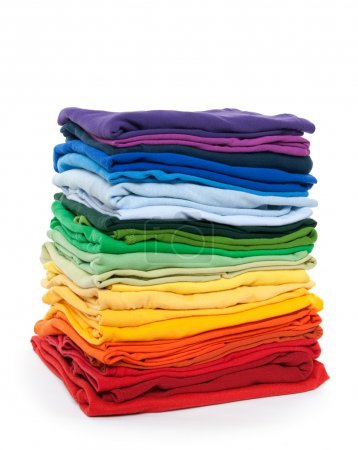 Rainbow clothes pile. Bright folded clothes on whi...