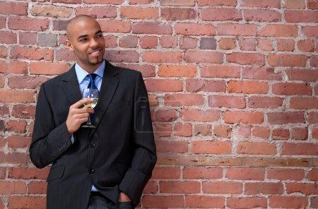 Photo pour Entreprise jeune homme appuyé contre le mur de brique, souriant et boire du vin souriant. - image libre de droit
