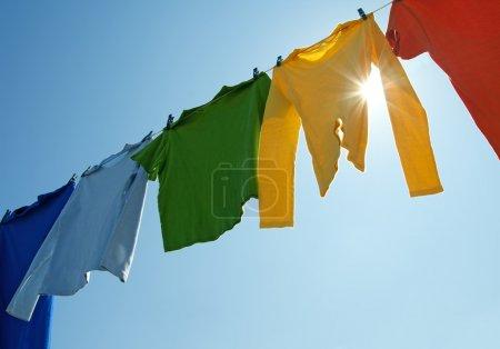 Photo pour Vêtements colorés suspendus pour sécher sur une corde à linge et le soleil qui brille dans le ciel bleu. - image libre de droit