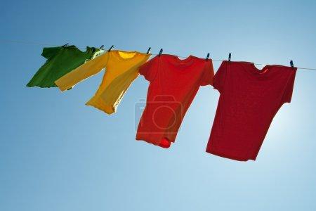 Photo pour Vêtements colorés suspendus pour sécher dans le ciel bleu, un jour ensoleillé et venteux. - image libre de droit
