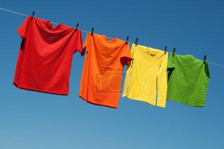 Photo pour Blanchisserie été joyeuse. t-shirts colorés sur un ciel bleu et la ligne de blanchisserie. - image libre de droit