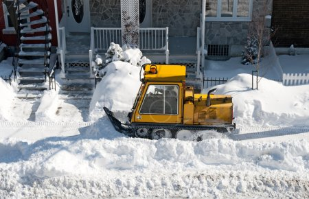 Yellow snowplough removing snow in the city