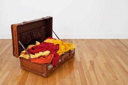 Photo pour Valise de cuir sur le plancher en bois, plein de vêtements orange, rouge et jaune. - image libre de droit