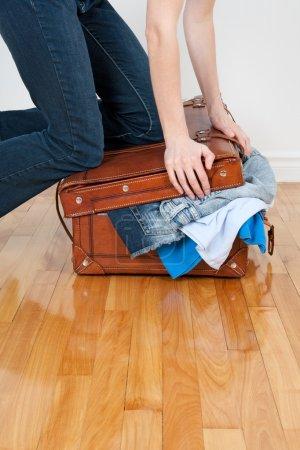 Photo pour Jeune femme en jeans essayant de fermer sa valise avec trop de vêtements . - image libre de droit