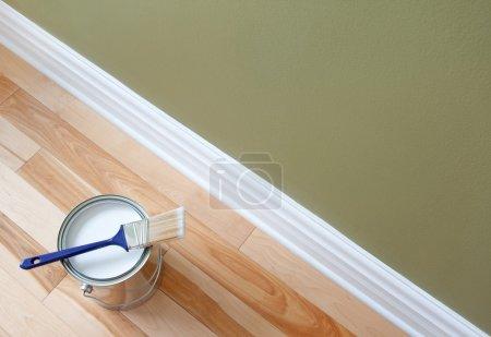 Photo pour Nouvellement ouvert canette de peinture blanche et pinceau sur plancher en bois. - image libre de droit