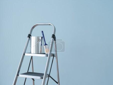 Photo pour Préparation peindre le mur. outils de peinture sur une échelle métallique. - image libre de droit