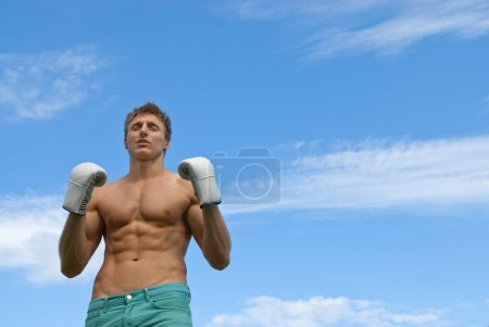 Athletic young man in boxing gloves