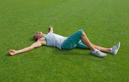 Sporty guy relaxing on green training field