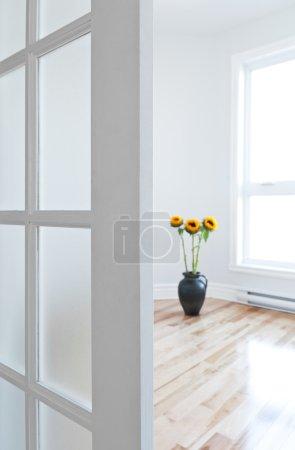 Photo pour Porte ouverte qui mène à une salle contemporaine pleine de lumière, décoré de fleurs. - image libre de droit